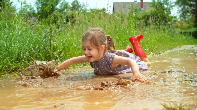 slo mo little girl lying in a puddle and moving her hands as if she were swimming - birichinata video stock e b–roll