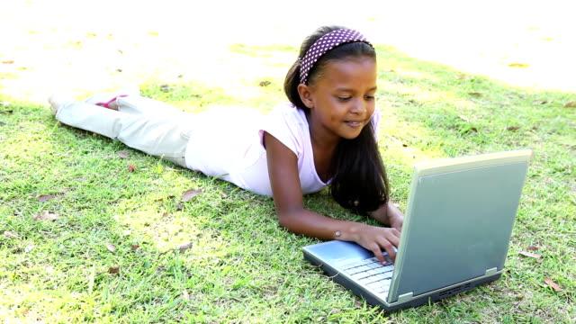 piccola ragazza sdraiata sull'erba utilizzando il computer portatile - 8 9 anni video stock e b–roll