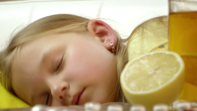 stockvideo's en b-roll-footage met little girl lying sick in her bed, coughing. - doordrukstrip