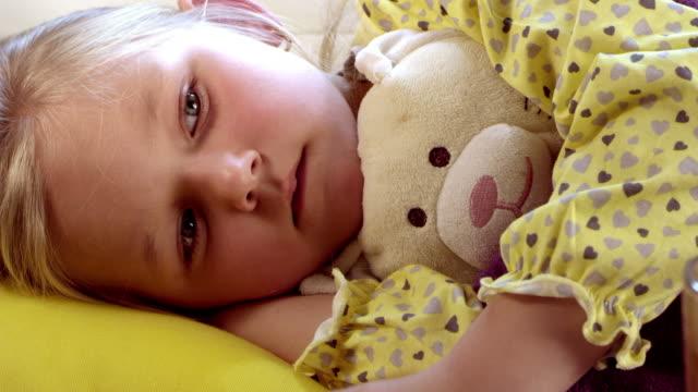 stockvideo's en b-roll-footage met little girl lying sick in her bed. - doordrukstrip