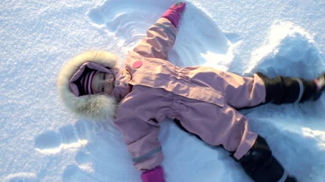 liten flicka gör en snöängel liggande i snön på en frostig solig dag - snow kids bildbanksvideor och videomaterial från bakom kulisserna