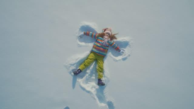 liten flicka att göra en ängel i snön - snow kids bildbanksvideor och videomaterial från bakom kulisserna