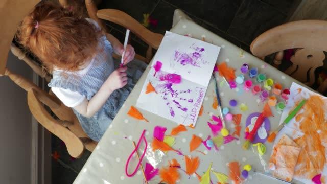 little girl making an easter card - sztuka i rzemiosło wytworzony przedmiot filmów i materiałów b-roll