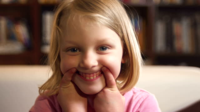 Little girl making faces while she video chats video