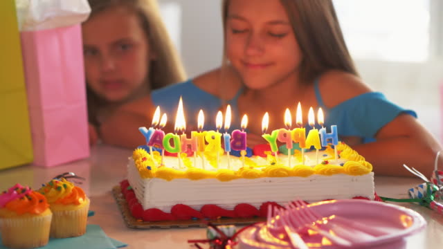 Little girl making wish at birthday party. video