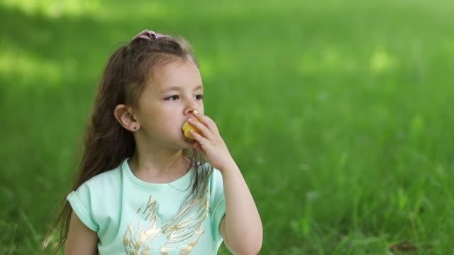 a little girl on a green lawn bites off a ripe apricot. portrait. - pesche bambino video stock e b–roll