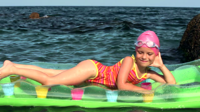 Niña en un colchón en el mar - vídeo