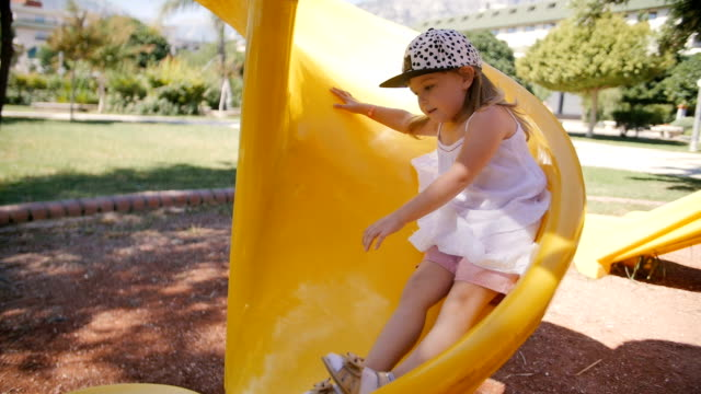 Little girl on curved slide, slow motion video