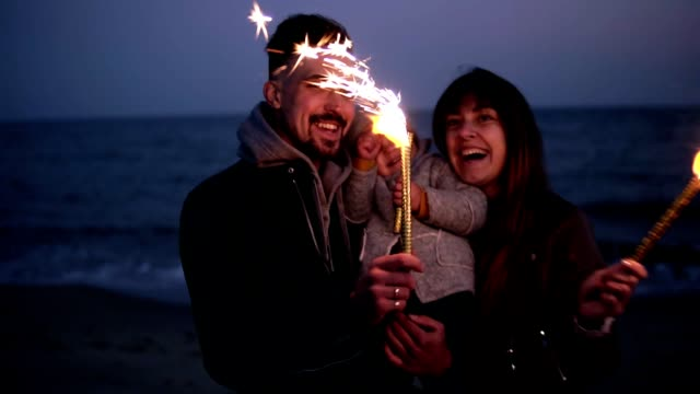 Little girl on father's arms watching her mother, father waving sparklers on the beach in the evening dusk. Happy young family video
