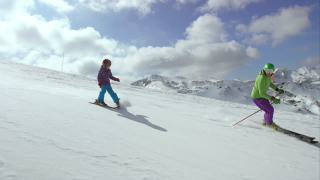 TS Little girl on skis skiing behind her ski instructor