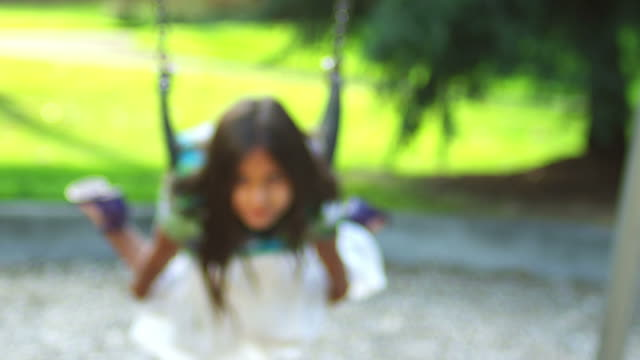 Little girl on swing sticks her tongue out. video