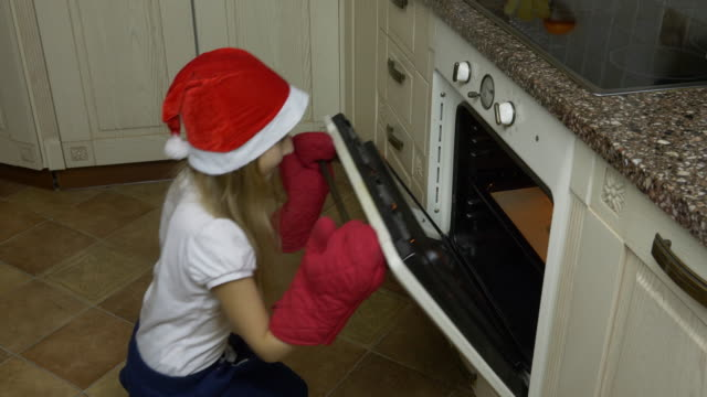 Little girl opens the oven. Ginger cookies are taken from the oven. The girl cooked Christmas cookies. She sniffs cookies and enjoys the scent. Happy little girl is smiling and looking at the camera. video