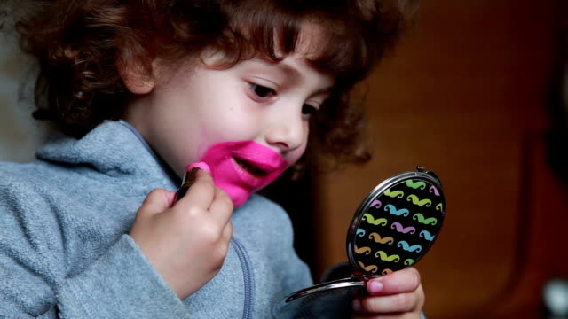 little girl painting her lips with lipstick and looking at pocket mirror - театральный грим стоковые видео и кадры b-roll
