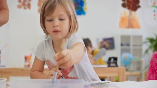 DS Little girl painting in the bright classroom