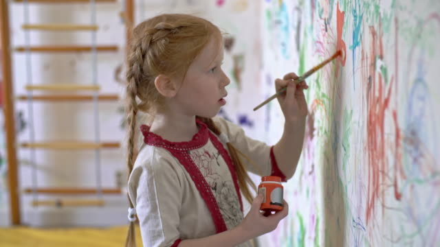 Little Girl Painting on Wall of her Room