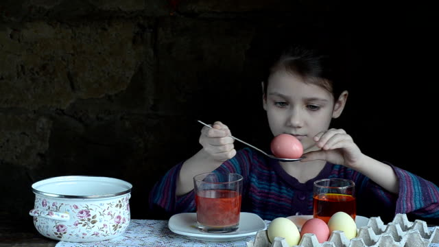 Little girl paints eggs for Easter, and puts it in the stand video