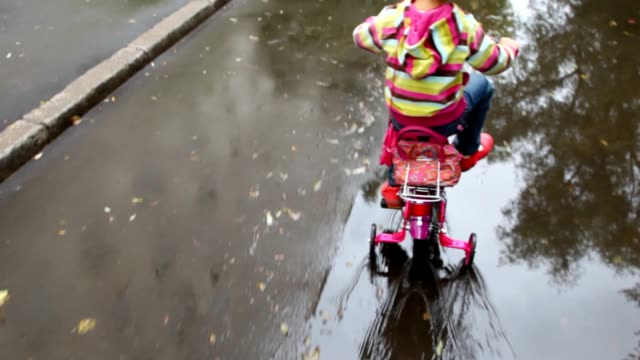 Little girl pedaling on wet asphalt with puddles video