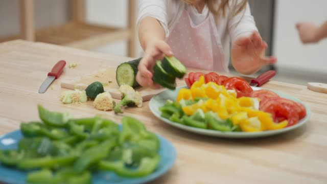 Little girl placing cucumber slices onto a plate and smiling