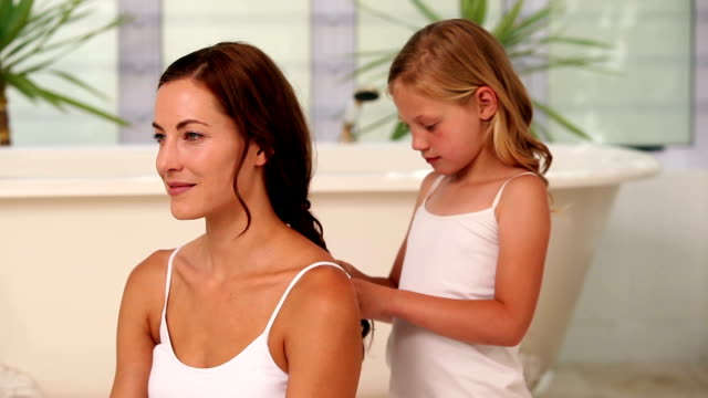 Little girl plaiting her mothers hair in the morning video