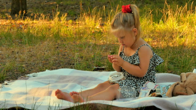 Little girl play with coins on blanket in park video