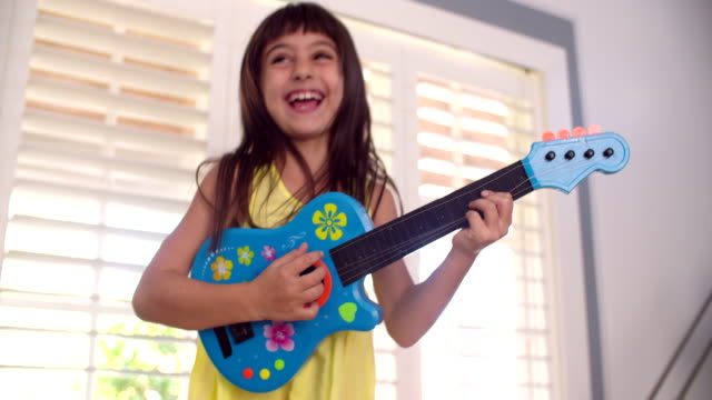 Little girl playing a guitar in the lounge video