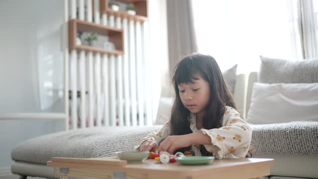 Little girl playing a toy in living room at home