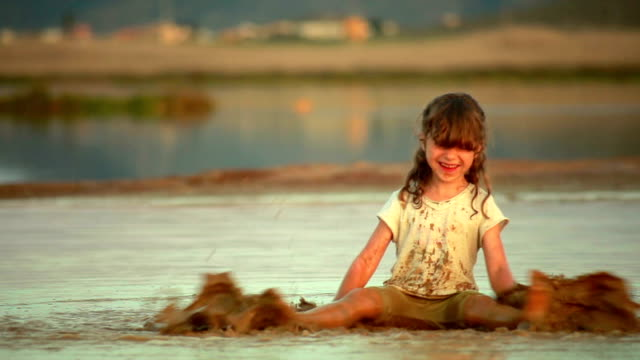 Little girl playing and splashing in the mud. Six year old Anna is playing in the mud at salinas in Spain. La Manga, Mar Menor. mud stock videos & royalty-free footage