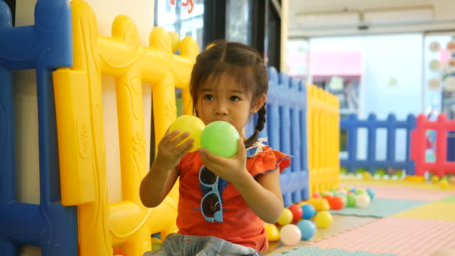 Little girl playing ball in playground room video
