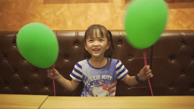 Little girl playing balloons video