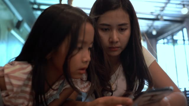 little girl playing digital tablet with mother