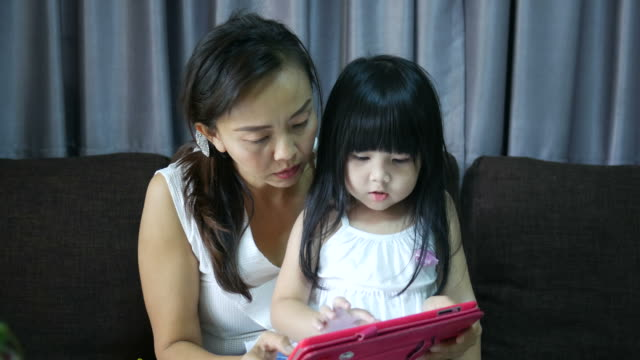 little girl playing digital tablet with mother video