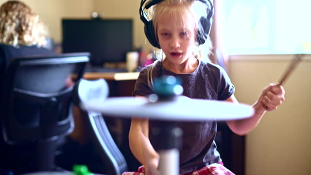 vídeos de stock e filmes b-roll de little girl playing drums when her sister doing homework - instrumental