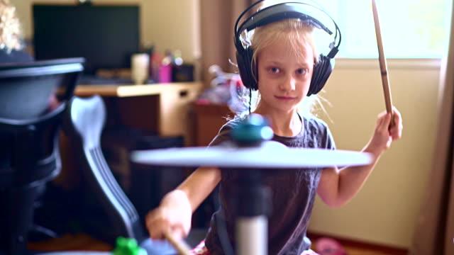 vídeos de stock, filmes e b-roll de menina tocando bateria quando a irmã dela fazendo lição de casa - praticando