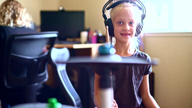 Little girl playing drums when her sister doing homework video