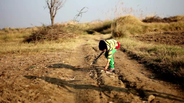 little girl playing gilli danda outdoor in the nature - haryana video stock e b–roll