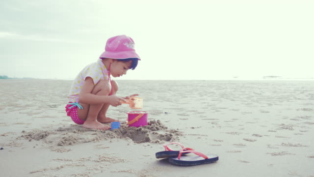 A little girl (6-7 years) playing in sand on beach video