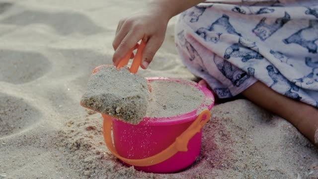 ein kleines mädchen mit schaufel und eimer am strand im sand spielen - eimer stock-videos und b-roll-filmmaterial
