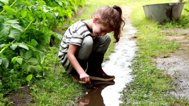 Little girl playing in the puddle in the backyard