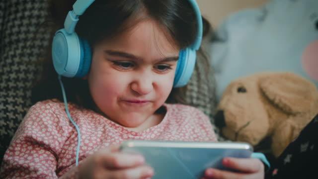 モバイルゲームをプレイ小さな女の子。幸せに彼女の携帯電話でゲームをプレイ。彼女は邪魔されるのを避けるためにヘッドフォンを使用しています。携帯電話でビデオゲームをプレイ5歳の - ゲーム ヘッドフォン点の映像素材/bロール