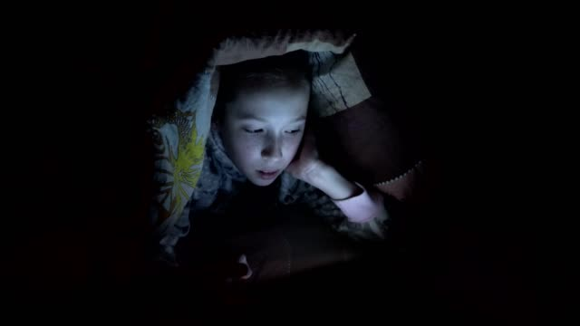 a little girl playing on a tablet at night on a bed under a blanket. concept video. close-up. raw video. 4k. - preadolescente video stock e b–roll