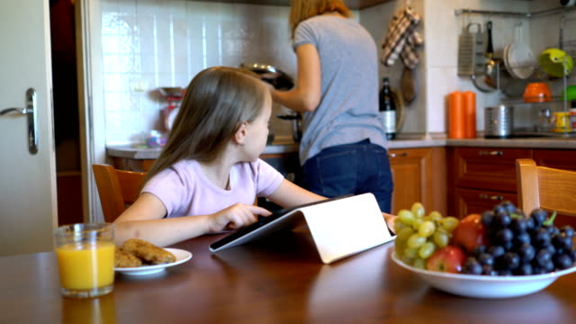 Little girl playing on her digital tablet at home. Young blond girl browsing and playing on the digital and asking her mother for help. surfing the net stock videos & royalty-free footage