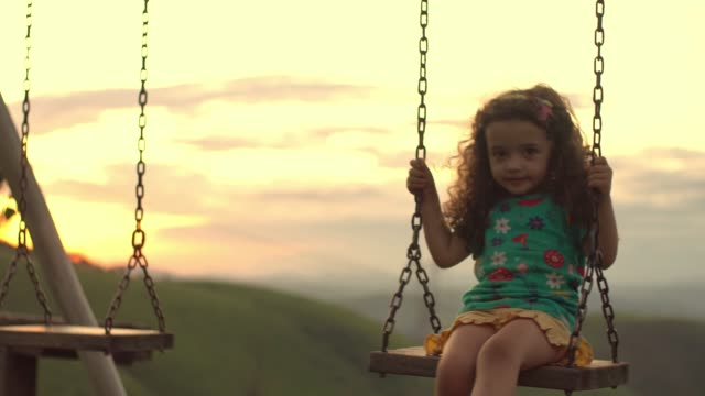 Little girl playing on the swing in the backlight