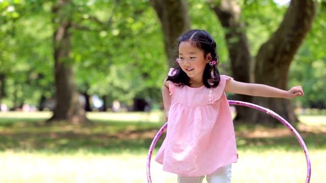 小女孩在玩塑膠圈 - 休閒器具 個影片檔及 b 捲影像