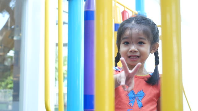 Little girl playing playground in park , posing victory sign video