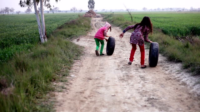 Little girl playing & running on country road with tyre video