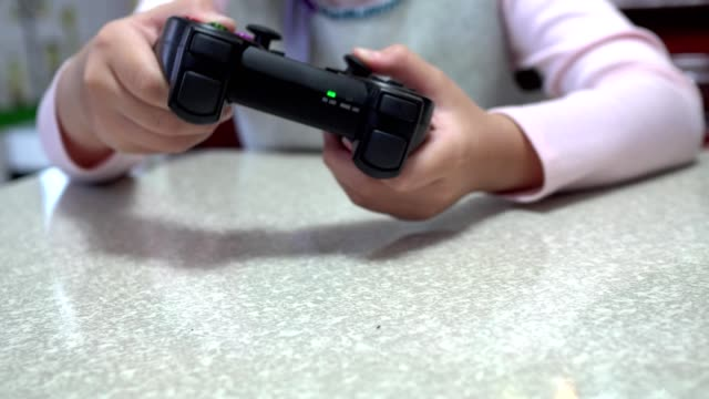 little girl playing video games with joystick. focus on hands. - kids holding hands filmów i materiałów b-roll