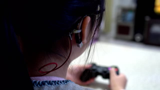 little girl playing video games with joystick. focus on hearing aid. - kids holding hands filmów i materiałów b-roll