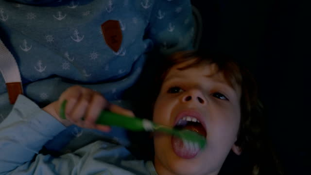 Little Girl Playing with a Toothbrush in her Mother's Lap video