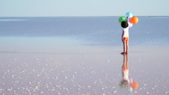 Little girl playing with colored balloons on the water video