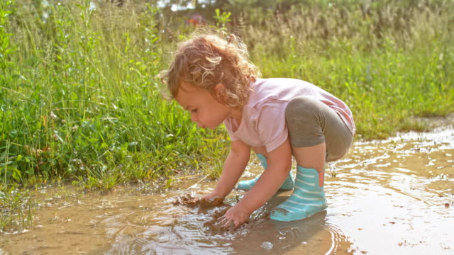SLO MO Little girl playing with her hands in the muddy puddle
